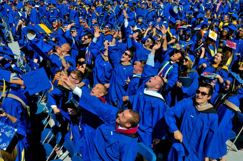 Graduates throw their caps at the University of Delaware's commencement ceremony as the future awaits; more than half of millennials in a study say they live paycheck to paycheck.