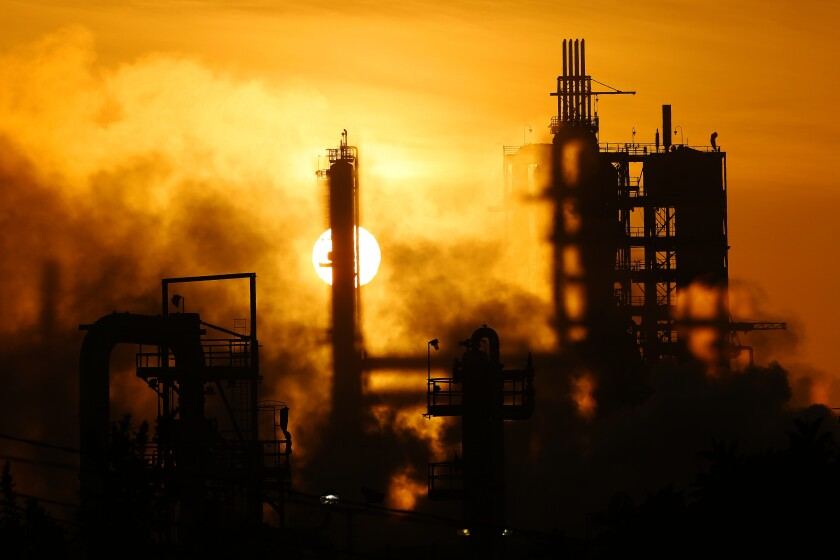 Sun sets behind the ConocoPhillips refinery in Wilmington