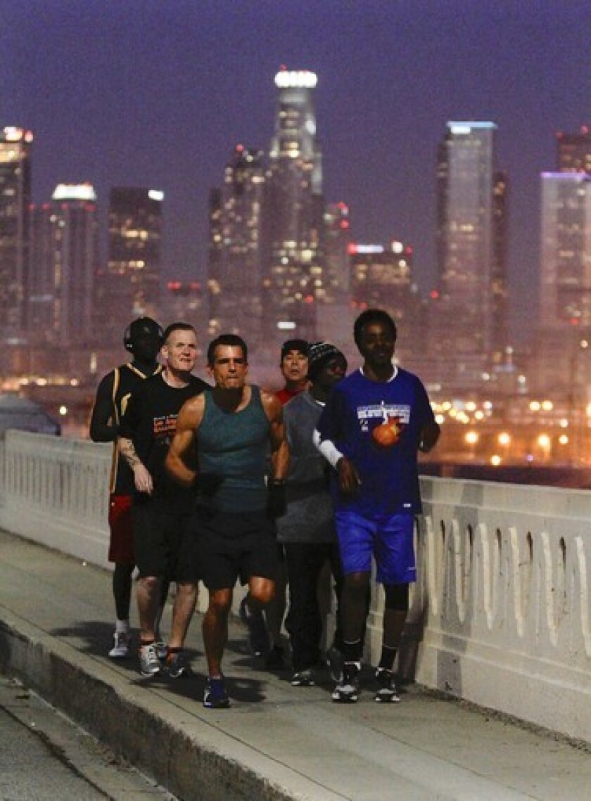L.A. County Superior Court Judge Craig Mitchell, center, leads a group of Midnight Mission residents on an early morning run across the 6th Street bridge.
