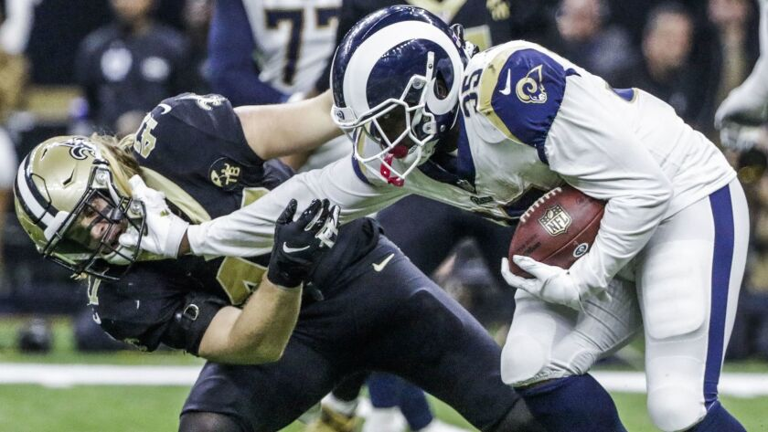 Rams cornerback Dominique Hatfield puts a hand to the face of Saints linebacker Alex Anzalone during Sunday's NFC championship game.