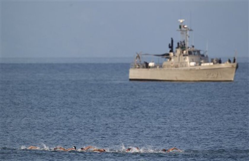 Swimmers stroke out to sea in their men's 10km open water swimming race at the Pan American Games in Puerto Vallarta, Mexico, Saturday Oct. 22, 2011. In the background is a Mexican Navy ship securing the area. (AP Photo/Eduardo Verdugo)