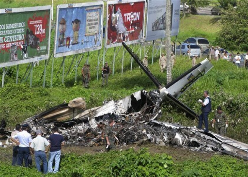 Workers look at a crashed plane in Recife, Brazil, Wednesday July 13, 2011. A regional airliner crashed in the northeastern city in Brazil Monday, killing all 16 people on board, the nation's Air Force said. The crew of the twin-turboprop aircraft belonging to Noar Airlines reported problems shortly after taking off about 7 a.m. local time from the city of Recife en route to the city of Natal. (AP Photo/Arnaldo Carvalho, JC Imagem)