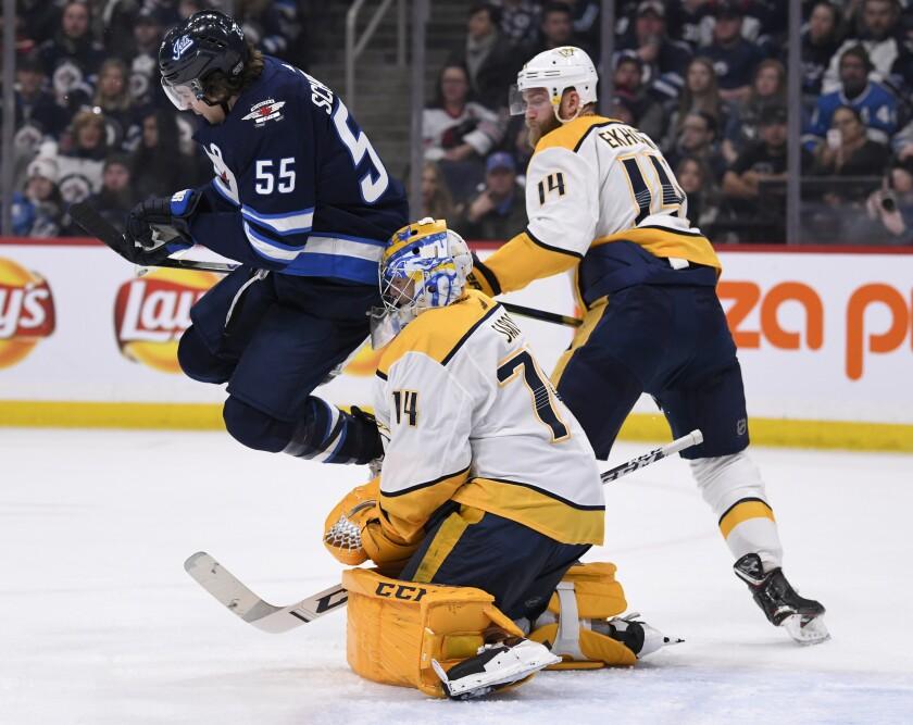Winnipeg Jets' Mark Scheifele (55) jumps out of the way of a shot in front of Nashville Predators goaltender Juuse Saros (74) during second period NHL hockey action in Winnipeg, Manitoba, Sunday Jan. 12, 2020. (Fred Greenslade/The Canadian Press via AP)