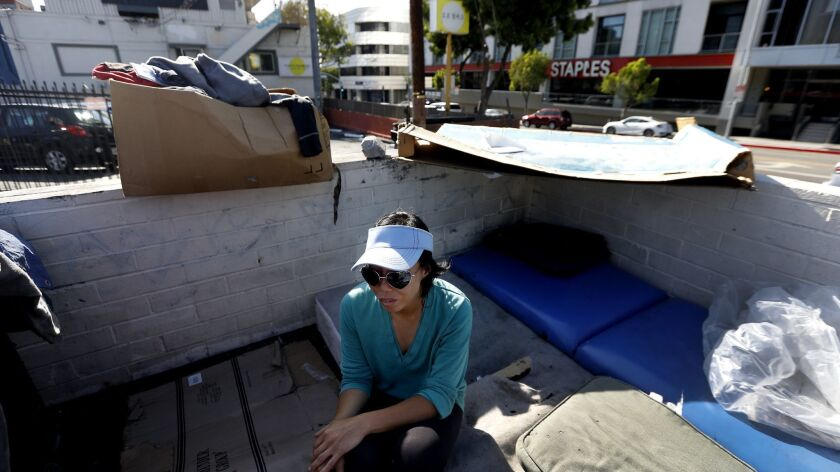 Denise Lee, 35, sits next to her tent in a parking lot near 6th and Vermont in the Koreatown neighborhood of Los Angeles on May 13.