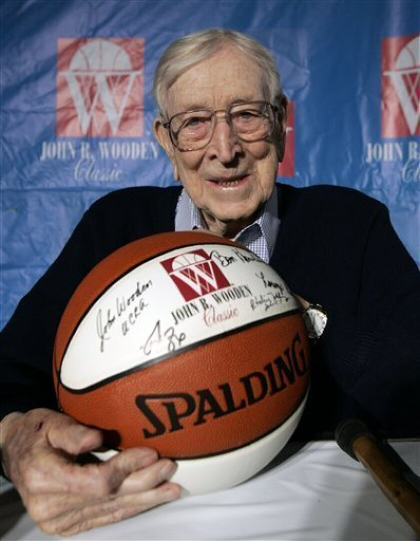 FILE - In this Dec. 9, 2005, file photo, Former UCLA basketball coach John Wooden poses for a picture after a news conference in Anaheim, Calif., about Saturday's Wooden Classic basketball tournament. Wooden, college basketball's gentlemanly Wizard of Westwood who built one of the greatest dynasties in all of sports at UCLA and became one of the most revered coaches ever, has died. He was 99. (AP Photo/Chris Carlson, File)