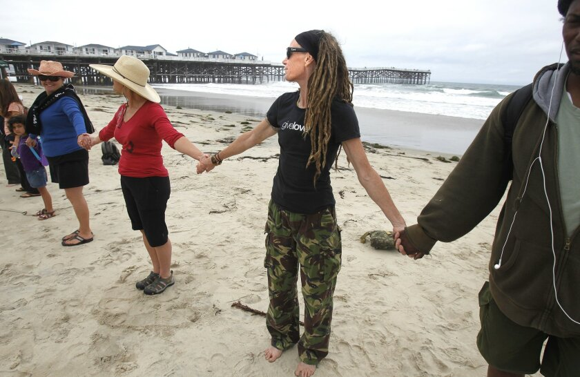 Anna Rumery (center) holds hands with fellow protesters near Crystal Pier Saturday, as part of the Hands Across the Sand environmental campaign.