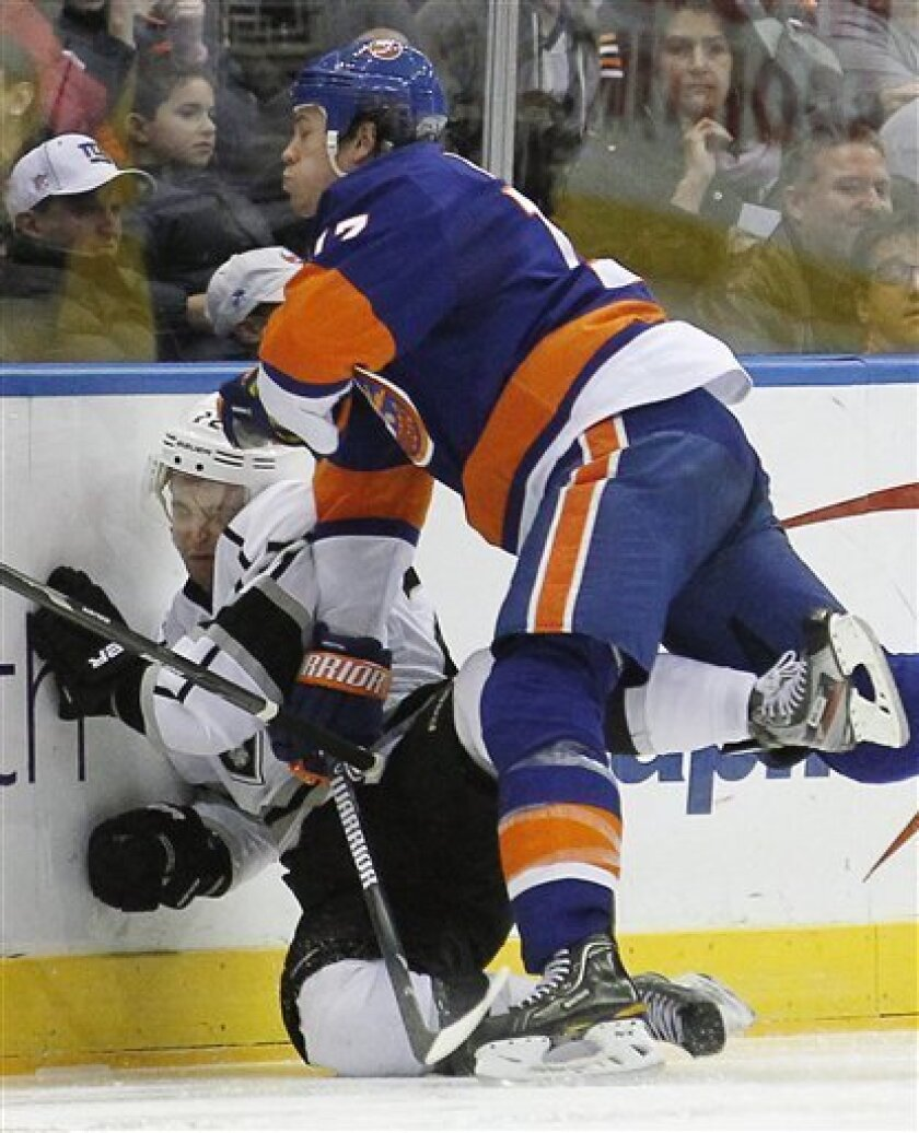 New York Islanders' Matt Martin (17) checks Los Angeles Kings' Trevor Lewis (22) into the boards during the third period of an NHL hockey game at the Nassau Coliseum in Uniondale, N.Y., Saturday, Feb. 11, 2012. The Islanders won 2-1 in overtime. (AP Photo/Paul J. Bereswill)