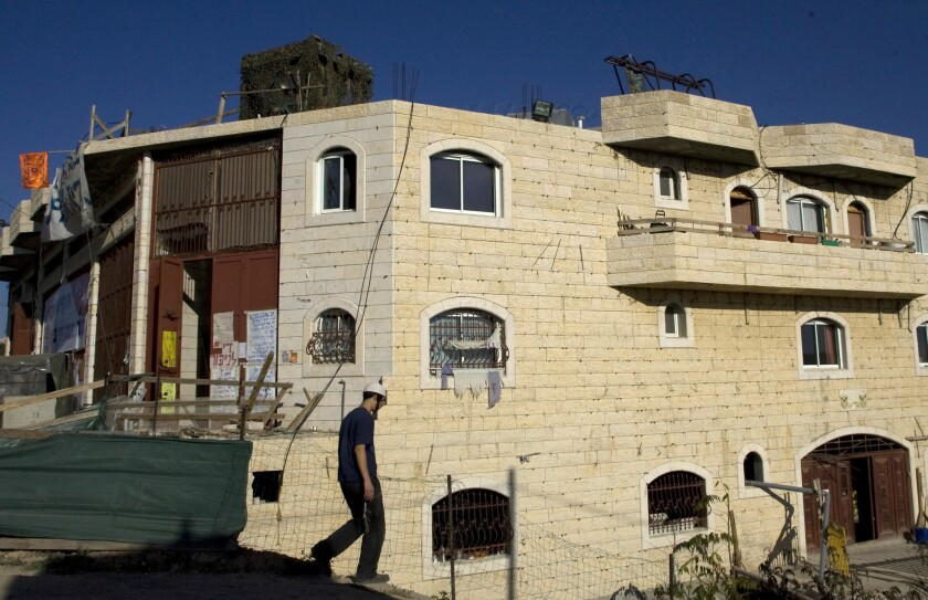 A Jewish settler walks outside a disputed building in the West Bank town of Hebron in 2008.