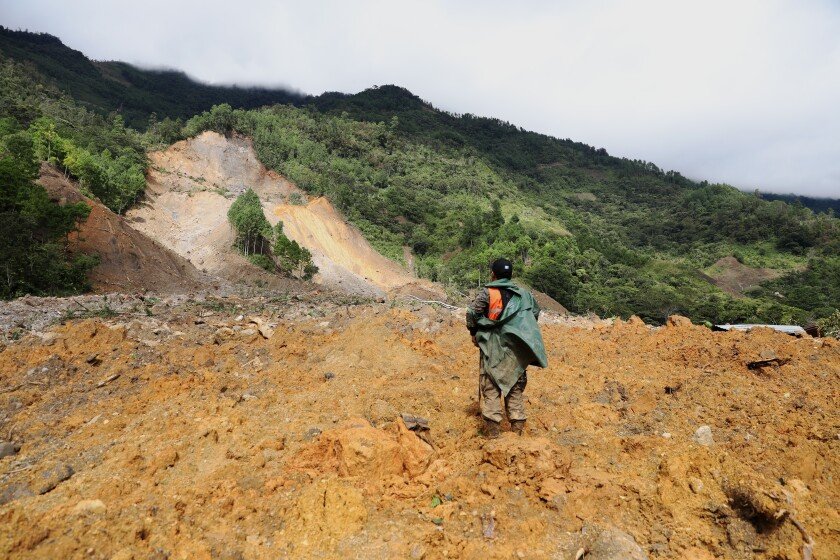 A member of a search and rescue team looks for survivors through the destruction caused by a massive, rain-fueled landslide in the village of Queja, in Guatemala, Saturday, Nov. 7, 2020, in the aftermath of Tropical Storm Eta. (Esteban Biba/Pool Photo via AP)