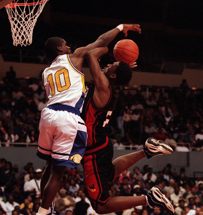 Crenshaw guard Kevin Bradley blocks a shot by Westchester's Albert Miller during the 1997 City Section championship basketball game at the L.A. Sports Arena.