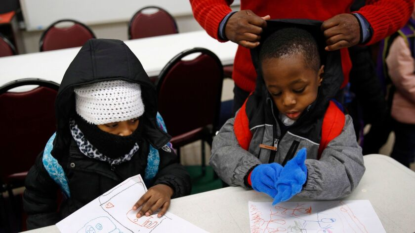 Pre-kindergarten students get bundled up at the end of the day as they wait to be picked up Tuesday at Lakewood Elementary School in Baltimore. Recent cold weather exposed the poor state of school buildings in many East Coast cities.