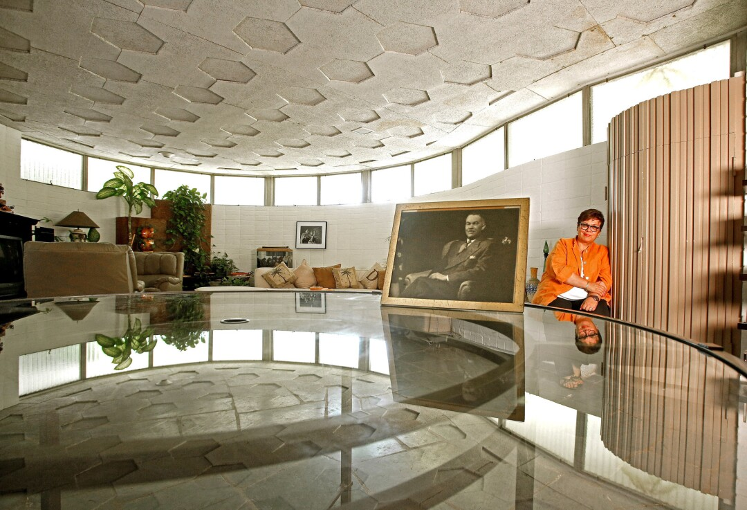 Karen Hudson sits in a curved room with a honeycomb ceiling before a photo of Paul R. Williams.