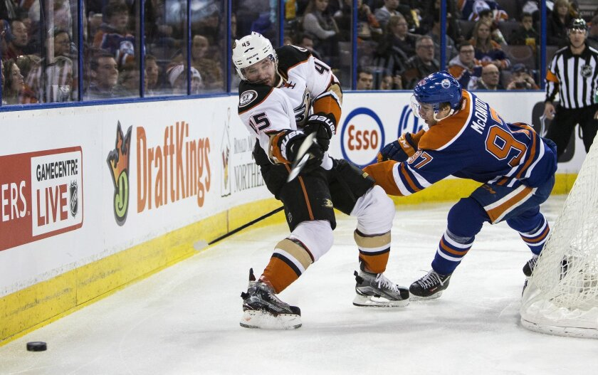 Anaheim Ducks' Sami Vatanen (45) shoots the puck away from Edmonton Oilers' Connor McDavid (97) during the second period of an NHL hockey game, Tuesday, Feb. 16, 2016 in Edmonton, Alberta. (Codie McLachlan/The Canadian Press via AP) MANDATORY CREDIT