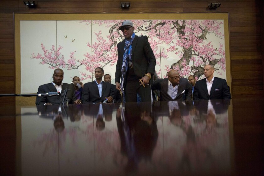 """Dennis Rodman stands up to leave after he and fellow US basketball players completed a television interview at a Pyongyang, North Korea hotel Tuesday, Jan. 7, 2014. Rodman came to the North Korean capital with a team of USA basketball stars for an exhibition game on Jan. 8, the birthday of North Korean leader Kim Jong Un. From left to right are Cliff Robinson, Jerry Dupree, Charles D. Smith, unidentified, Vin Baker, Andre """"Silk"""" Poole and Doug Christie. (AP Photo/David Guttenfelder)"""