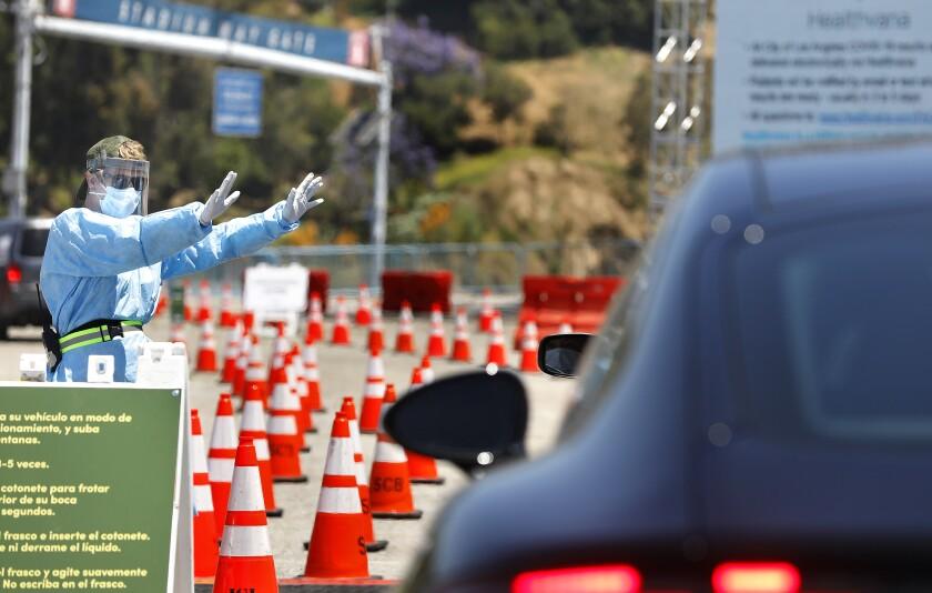 Worker directs traffic at drive-through coronavirus testing site at Dodger Stadium