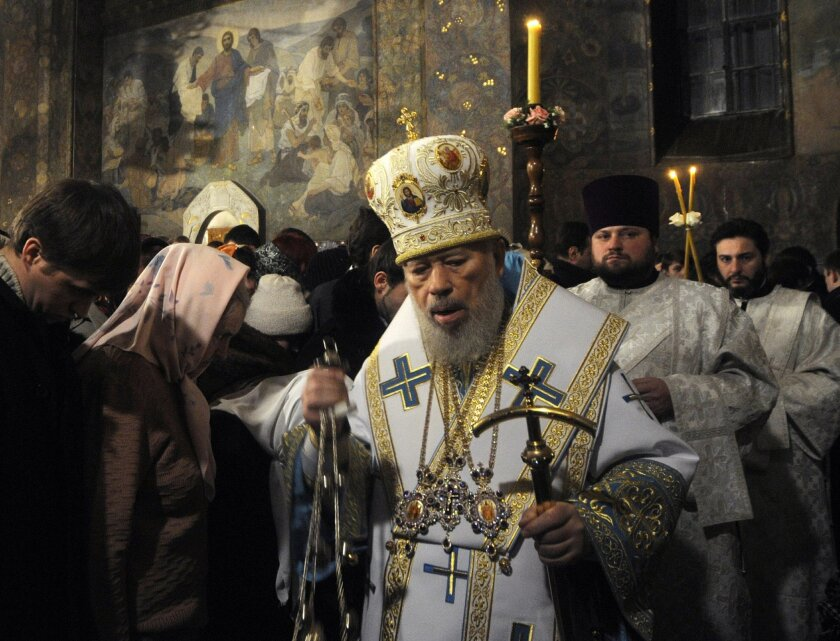 CORRECTS STYLE OF NAME TO VOLODYMYR -FILE - In this file photo taken on Saturday, Jan. 5, 2014, the head of the Ukrainian Orthodox Church under the Moscow Patriarchate, Volodymyr, foreground, leads services during the Christmas Eve mass in the Kyiv-Pechersk Lavra church in Kiev, Ukraine. The head of Ukraine's Orthodox Church under the Moscow patriarchate died on Saturday, July 5, 2014, the patriarchate said on its website. Volodymyr, 78, ascended to the leadership of the Ukrainian Orthodox Church following the schism, during which its previous head was defrocked. Volodymyr suffered from internal bleeding and had been treated at a clinic in Kiev, Interfax reported. (AP Photo/Sergei Chuzavkov, file)