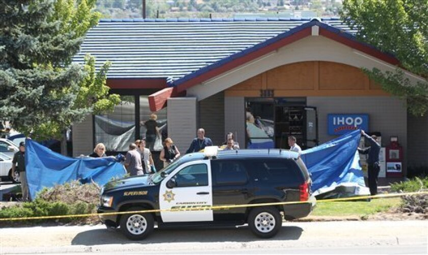 Officials investigate the scene of a shooting in an IHOP restaurant in Carson City, Nev., on Tuesday, Sept. 6, 2011. A gunman with a rifle opened fire at a International House of Pancakes restaurantkilling three people including two uniformed National Guard members and himself, and wounding six others in a hail of gunfire during the morning breakfast hour, authorities and witnesses said. (AP Photo/Cathleen Allison)