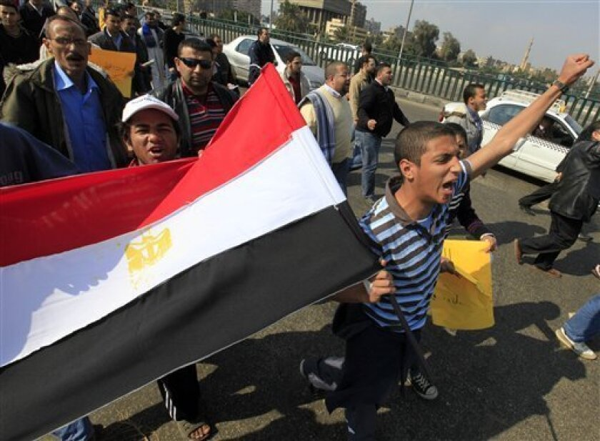 Anti-government protesters wave an Egyptian flag during a march in Cairo, Egypt, Friday, Feb. 11, 2011. Egypt's powerful military backed President Hosni Mubarak's plan to stay in office until September elections, but massive crowds outraged by his refusal to step down packed squares in Egypt's two