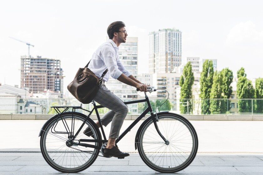 man in office work clothes commuting on bicycle