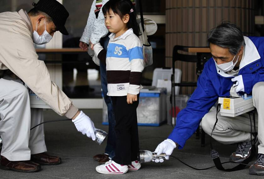 Three-year-old Wakana Nemoto is screened for radiation exposure in Fukushima, Japan, in April 2011, a month after the nuclear plant disaster. Infants who lived in the vicinity at the time face the greatest additional cancer risk during their lifetimes, a World Health Organization report said.