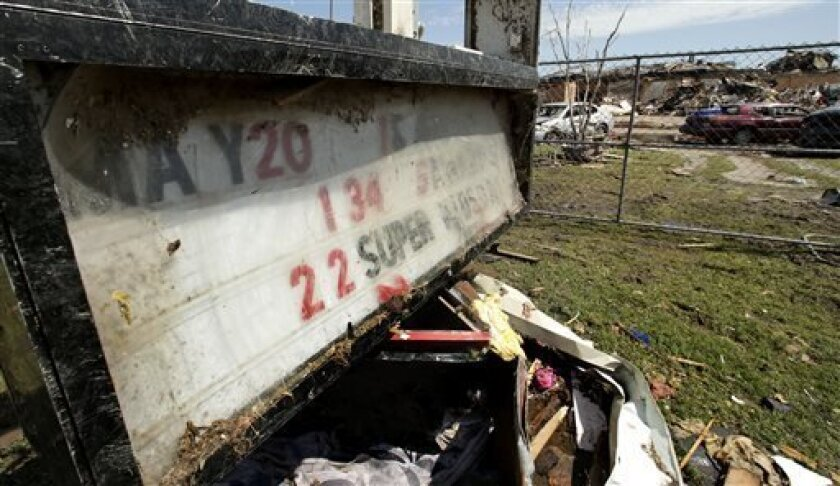 A battered event sign stands outside the wreckage of Plaza Towers Elementary School, where seven children were killed earlier in the week when a tornado hit Moore, Okla., Thursday, May 23, 2013. Cleanup continues three days after a huge tornado roared through the Oklahoma City suburb, flattening a