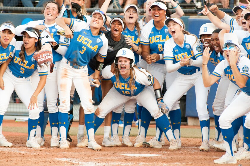 UCLA teammates wait for Malia Quarles at home plate after she hit a solo homerun to take the lead ag