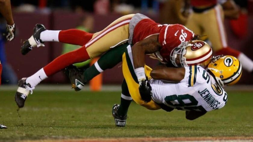 San Francisco 49ers' Dashon Goldon tackles Green Bay Packers' Greg Jennings in a 2013 game. Goldon just sold an Encino home.