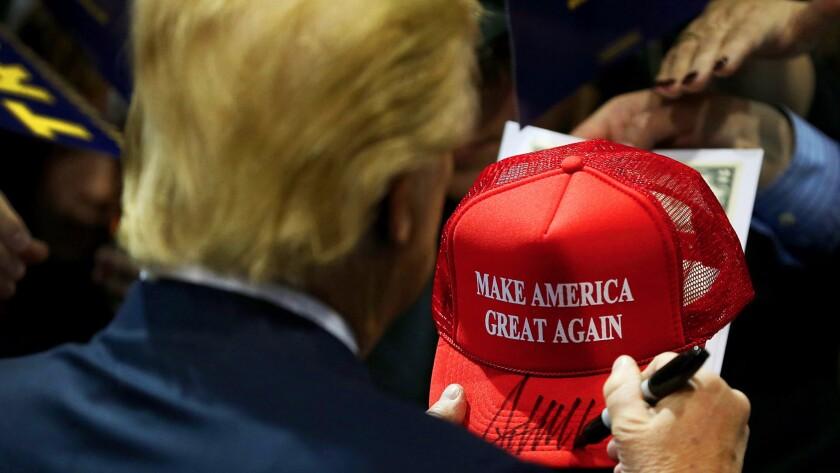 Donald Trump signs a campaign hat