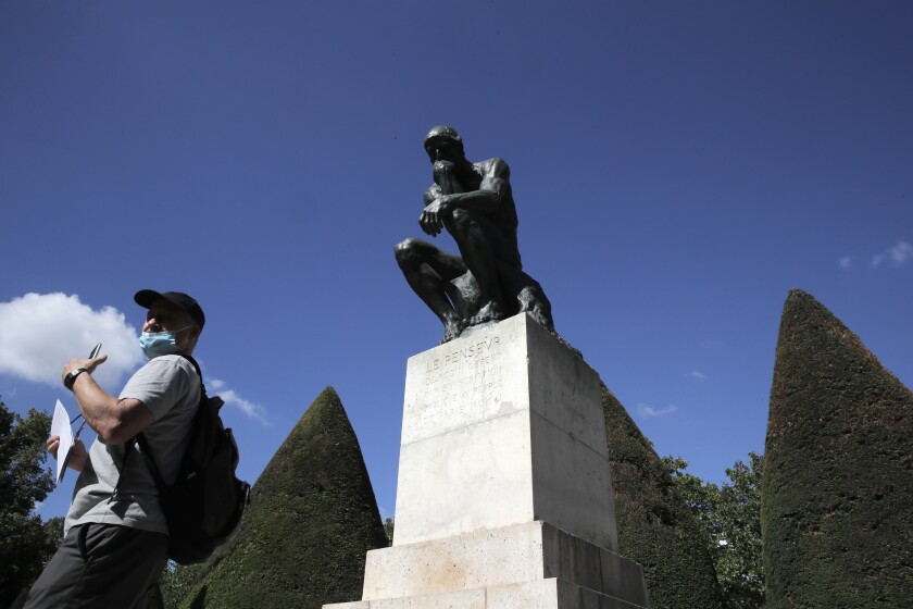 "A visitor walks past ""Le Penseur"" (The Thinker) by French sculptor Auguste Rodin in Paris Tuesday, July 7, 2020. The Musee Rodin is reopening this Tuesday morning albeit with a worrying loss of visitors and income caused by the four-months closure. Museum director, Catherine Chevillot, estimates the loss incurred by the crisis to be around 4.4 million euros (4.9 US dollars). and alleviated by the 1.4 million euro sales of bronze editions of Rodin statues. The museum doesn't sell Rodin statue originals but can sell 12 bronze replica editions of each of them, as it has been for 100 years. (AP Photo/Christophe Ena)"