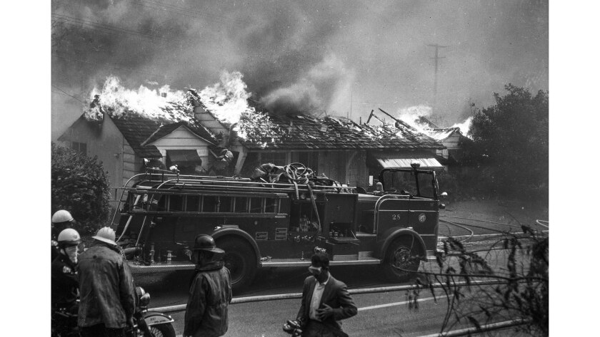 Firefighters are not able to save a home on Roscomare Road in 1961. The same area was threatened by fire in 2017.