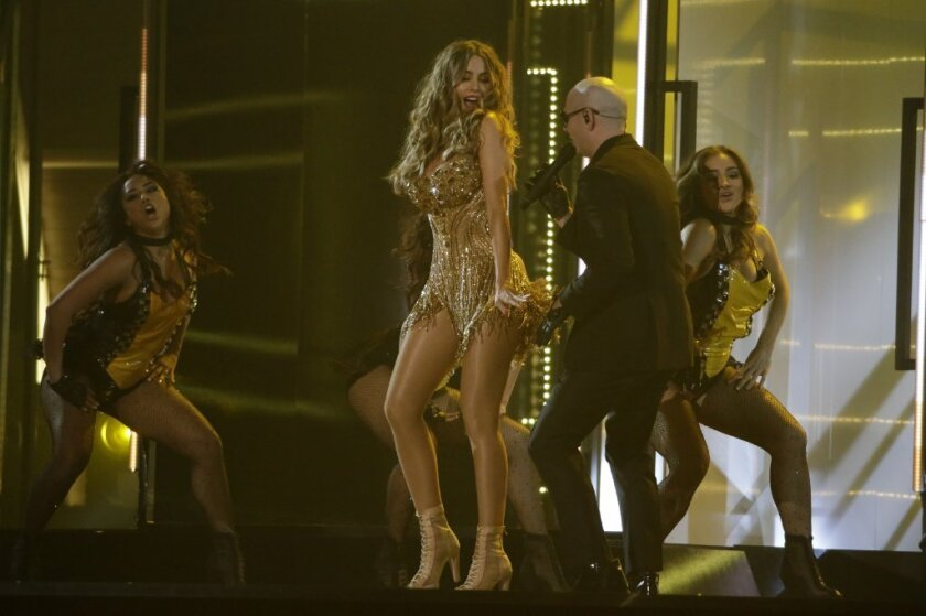 Sofia Vergara dances at the Grammy Awards wearing a gold-encrusted bustier with a Swarovski crystal-fringed flounce and a flame-beaded bodice designed by L.A. designer Mark Zunino as Pitbull performs.