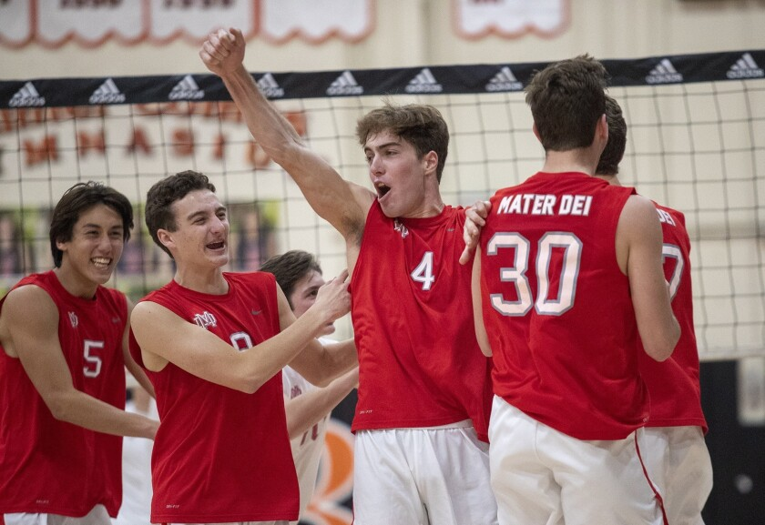 Mater Dei's David Linkletter (4) celebrates a kill shot from his teammate Joey Farney, right, during