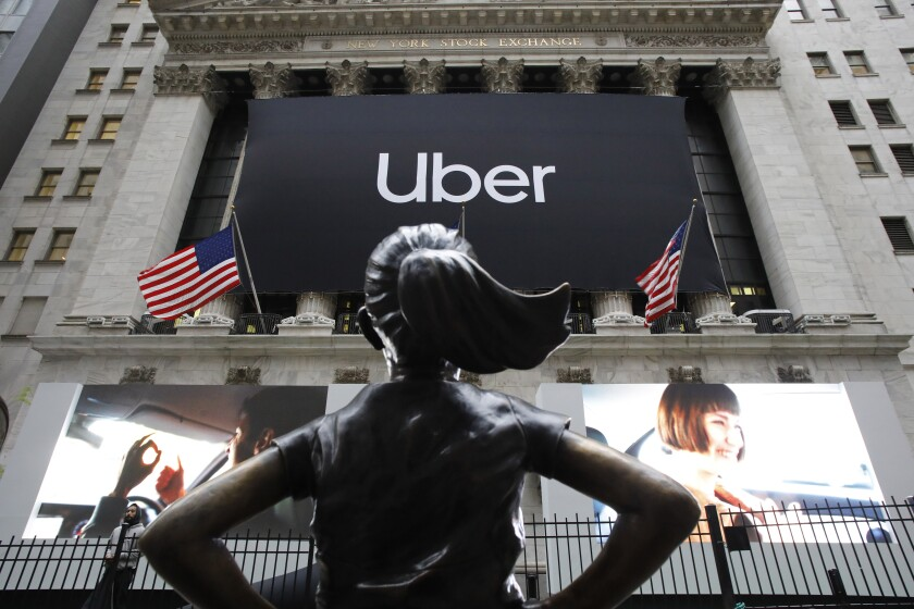 FILE - In this May 10, 2019, file photo the statue of Fearless Girl stands in front of the New York Stock Exchange before Uber holds its initial public offering. Uber reports financial results Monday, Nov. 4. (AP Photo/Mark Lennihan, File)
