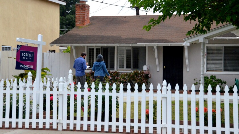 A real estate agent escorts his client into a home for sale in Costa Mesa on Saturday, April 24, 2021.