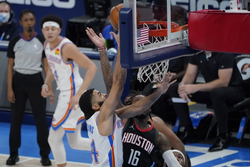 Oklahoma City Thunder guard Kenrich Williams, left, shoots in front of Houston Rockets guard Ben McLemore (16) during the first half of an NBA basketball game Wednesday, Feb. 3, 2021, in Oklahoma City. (AP Photo/Sue Ogrocki)