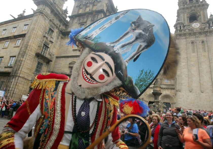 A man in a traditional costume and mask poses during carnival at the UNESCO World Heritage site of Santiago de Compostela in Spain.