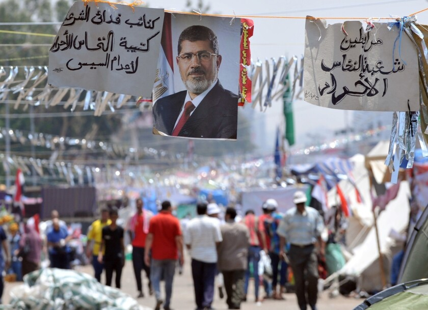 Supporters of Egypt's deposed President Mohamed Morsi walk past his portrait in Cairo on Tuesday during a sit-in outside Rabaa Al Adawiya mosque.