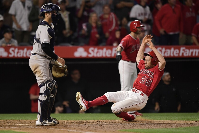 Angels' Peter Bourjos, right, scores as New York Yankees catcher Kyle Higashioka stands at the plate during the 12th inning on April 22.