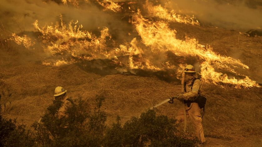 Two firefighters confront flames along Kagel Canyon Street in Lakeview Terrace.