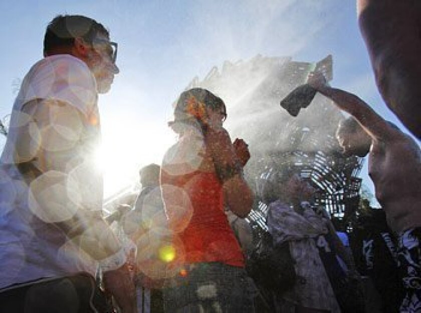 Concertgoers felt the mist from water canons as temperatures soared to 100 degrees. (Seam M. Haffey / Union-Tribune)