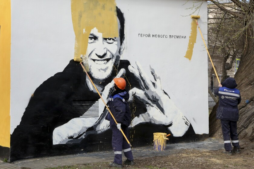 FILE - In this April 28, 2021, file photo, municipal workers paint over an image of Russia's imprisoned opposition leader Alexei Navalny in St. Petersburg, Russia. In the months before the Sept. 19 parliamentary election in Russia, authorities unleashed an unprecedented crackdown on the opposition, making sure the best-known and loudest Kremlin critics didn't run. Navalny, Putin's biggest critic who dented United Russia's dominance in regional legislatures in recent years, is serving a 2½-year prison sentence for violating parole for a conviction he says was politically motivated. (AP Photo/Valentin Egorshin, File)