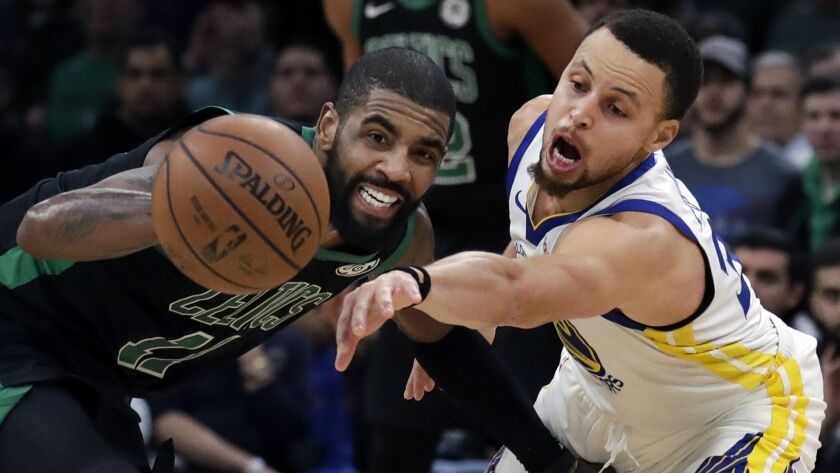Golden State Warriors guard Stephen Curry, right, attempts to steal the ball from Boston Celtics guard Kyrie Irving (11) in the fourth quarter.