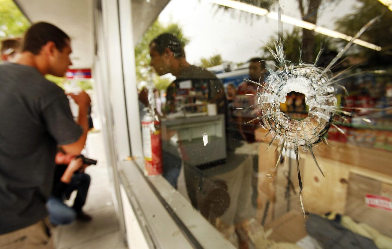 People look through a window pocked with bullet holes at the IV Deli Mart in Isla Vista, near UC Santa Barbara.