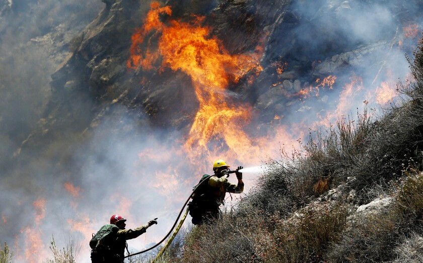 Firefighters battle a spot fire along Soledad Canyon Road near Agua Dulce on Tuesday.