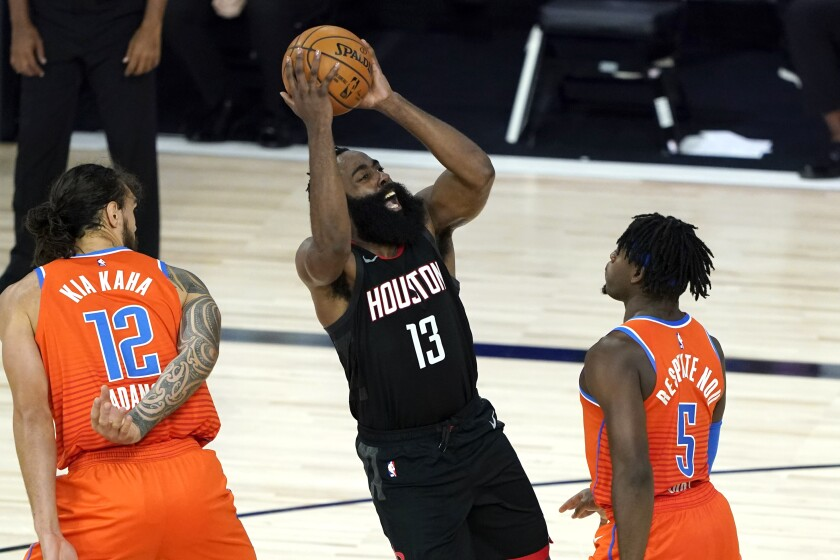 The Rockets' James Harden shoots over the Thunder's Luguentz Dort (5) and Steven Adams on Aug. 29, 2020.