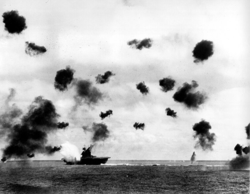Smoke billows from the USS Yorktown after a Japanese bomber hit the aircraft carrier in the Battle of Midway near Midway Islands in June 1942 during World War II.  Bursts from anti-aircraft fire fill the air.  ( AP Photo/U.S. Navy)