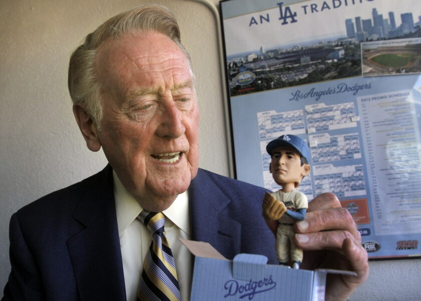 Dodgers broadcaster Vin Scully holds a Sandy Koufax bobblehead doll on August 7, 2012, the 47th anniversary of his call of the legendary pitcher's perfect game.