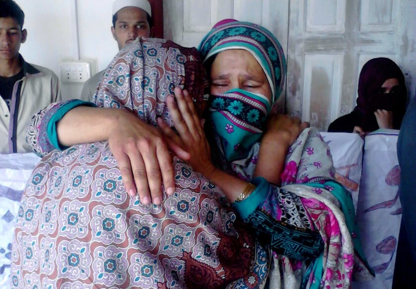 Pakistani family members of a female teacher who was beaten and set on fire, comfort each other in Upper Dewal, Pakistan, Thursday, June 2, 2016. Pakistani police say they have arrested two suspects and are continuing their search for five men who tortured a 19-year-old school teacher and burned he