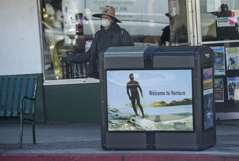 A woman wears a protective mask at a bus stop in downtown Ventura on March 30. Most businesses on Main Street are closed as a result of the coronavirus outbreak.