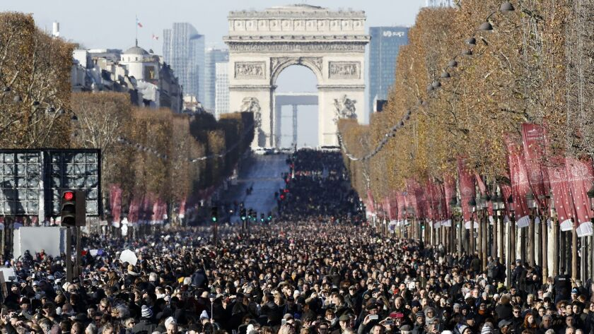 Vast crowds fill the streets of Paris on Dec. 9 to watch the funeral cortege of late French rock legend Johnny Hallyday.